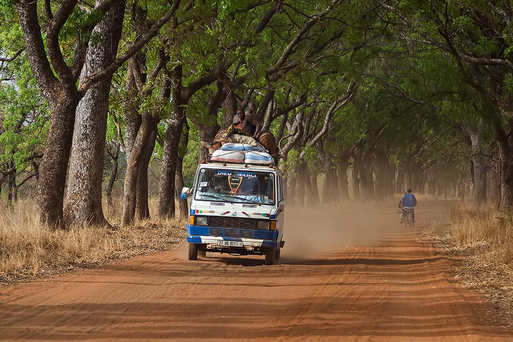 bush-taxi-driving-through-alley-of-trees-banfora-burkina-faso-africa-featured