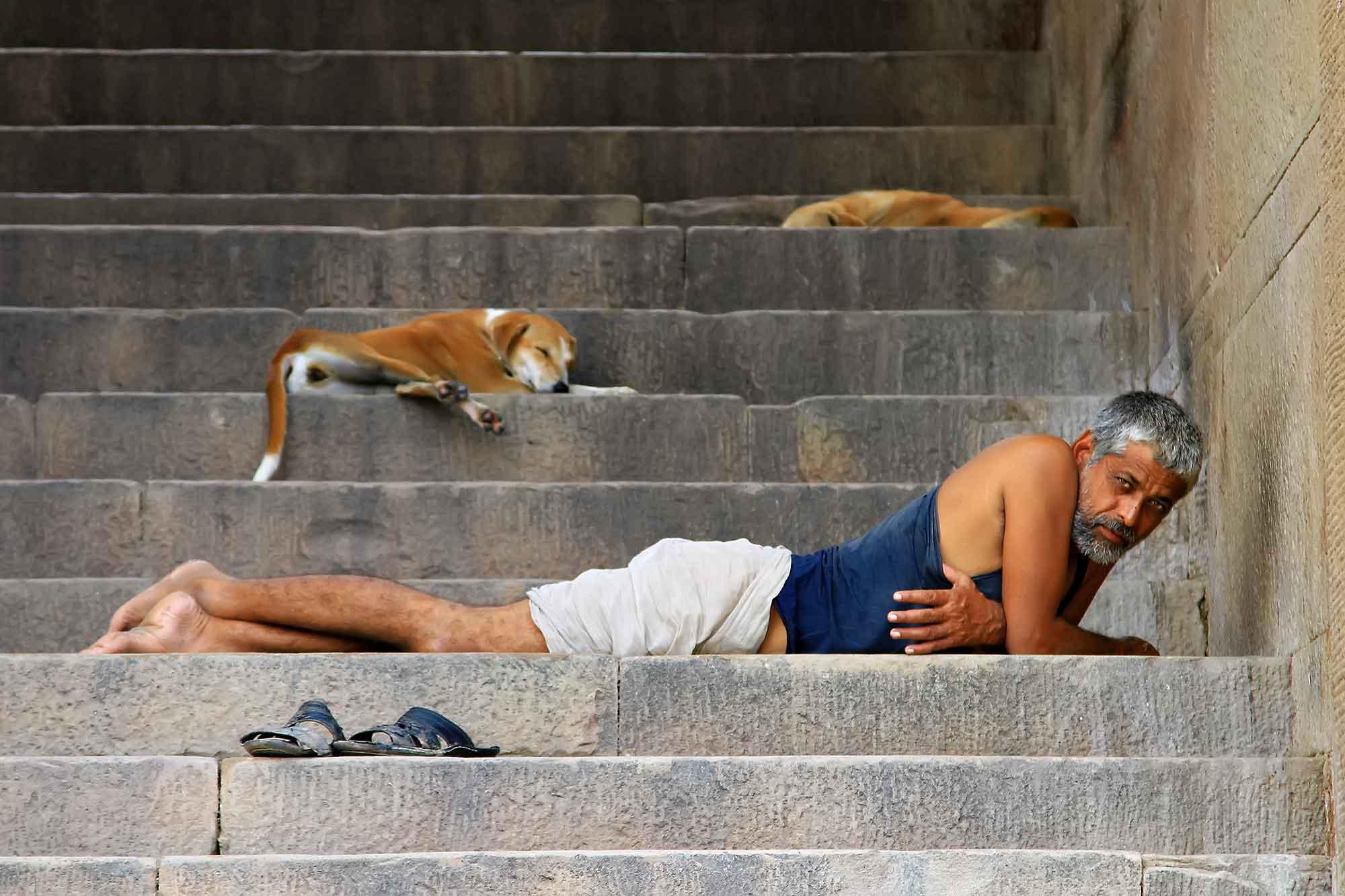 man-resting-stairs-ghats-varanasi-india