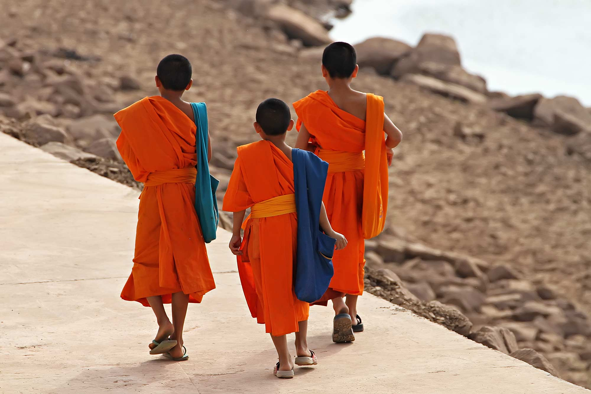 monks-walking-along-the-mekong-vientiane-laos