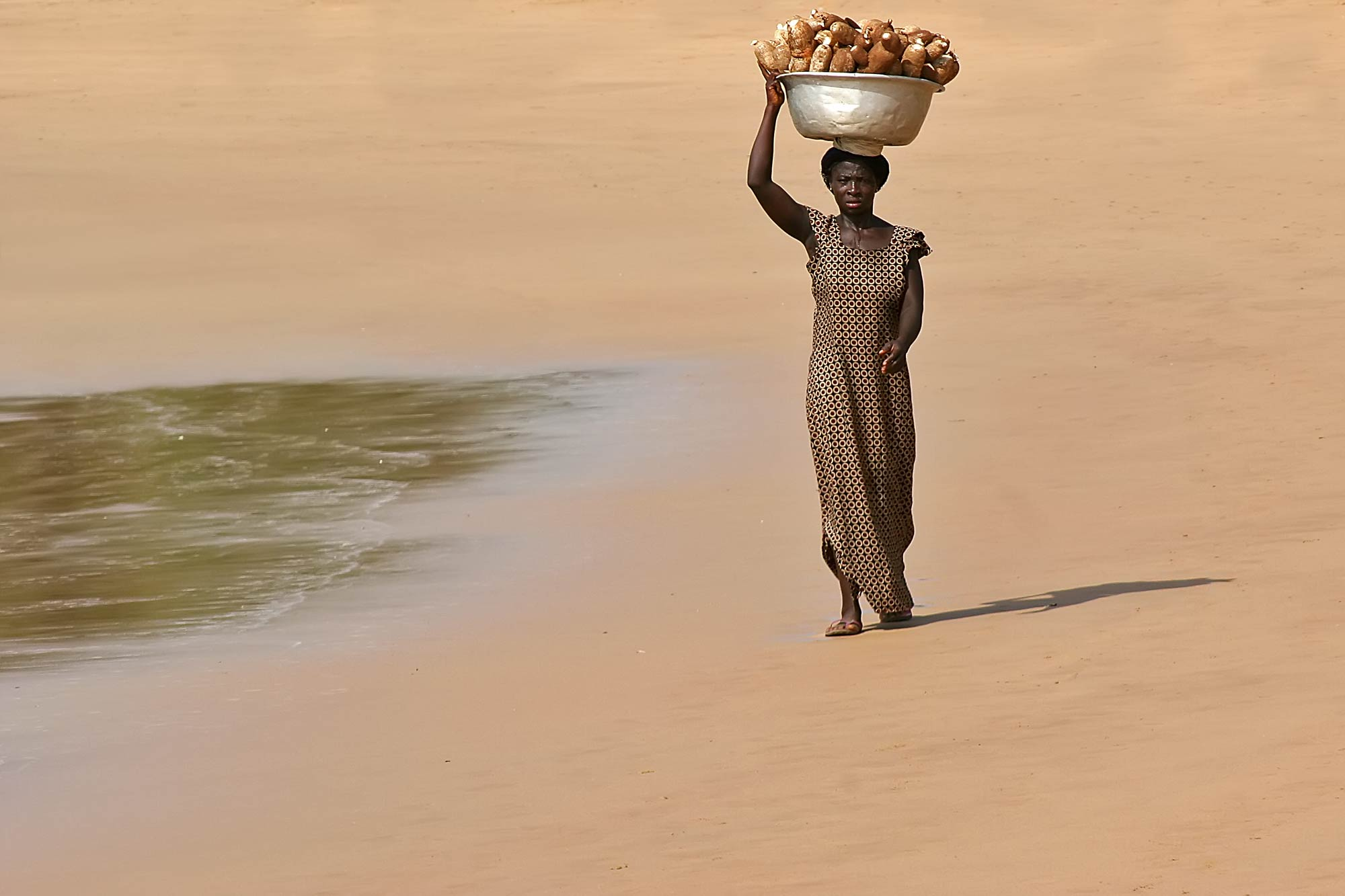 woman-walking-on-takoradi-beach-ghana-africa