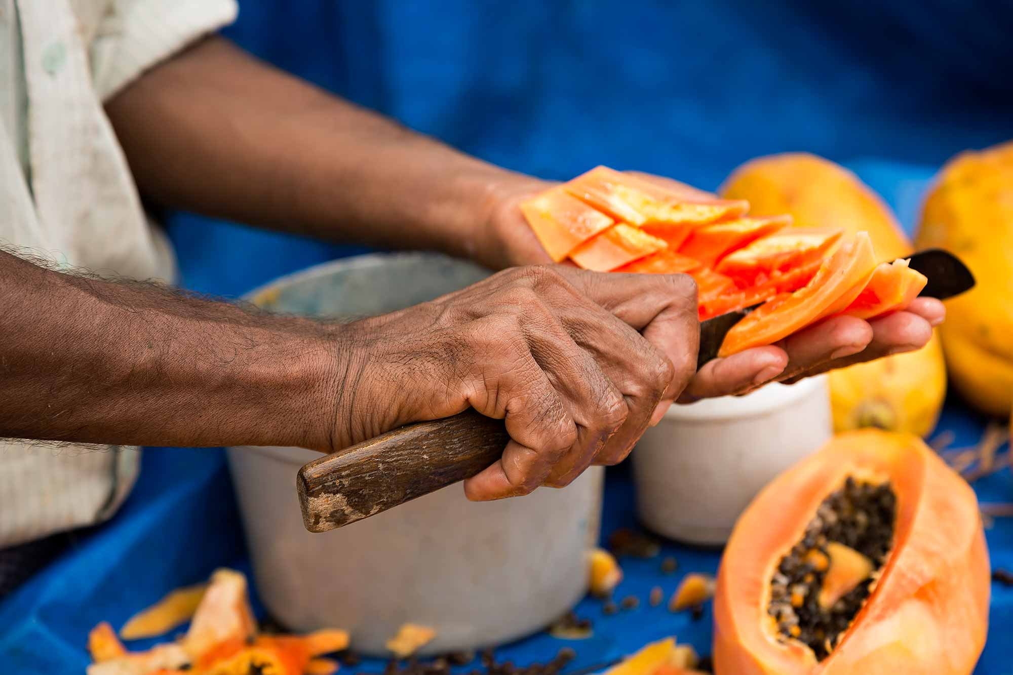 Man cutting papaya in the streets of Varanasi, India. © Ulli Maier & Nisa Maier