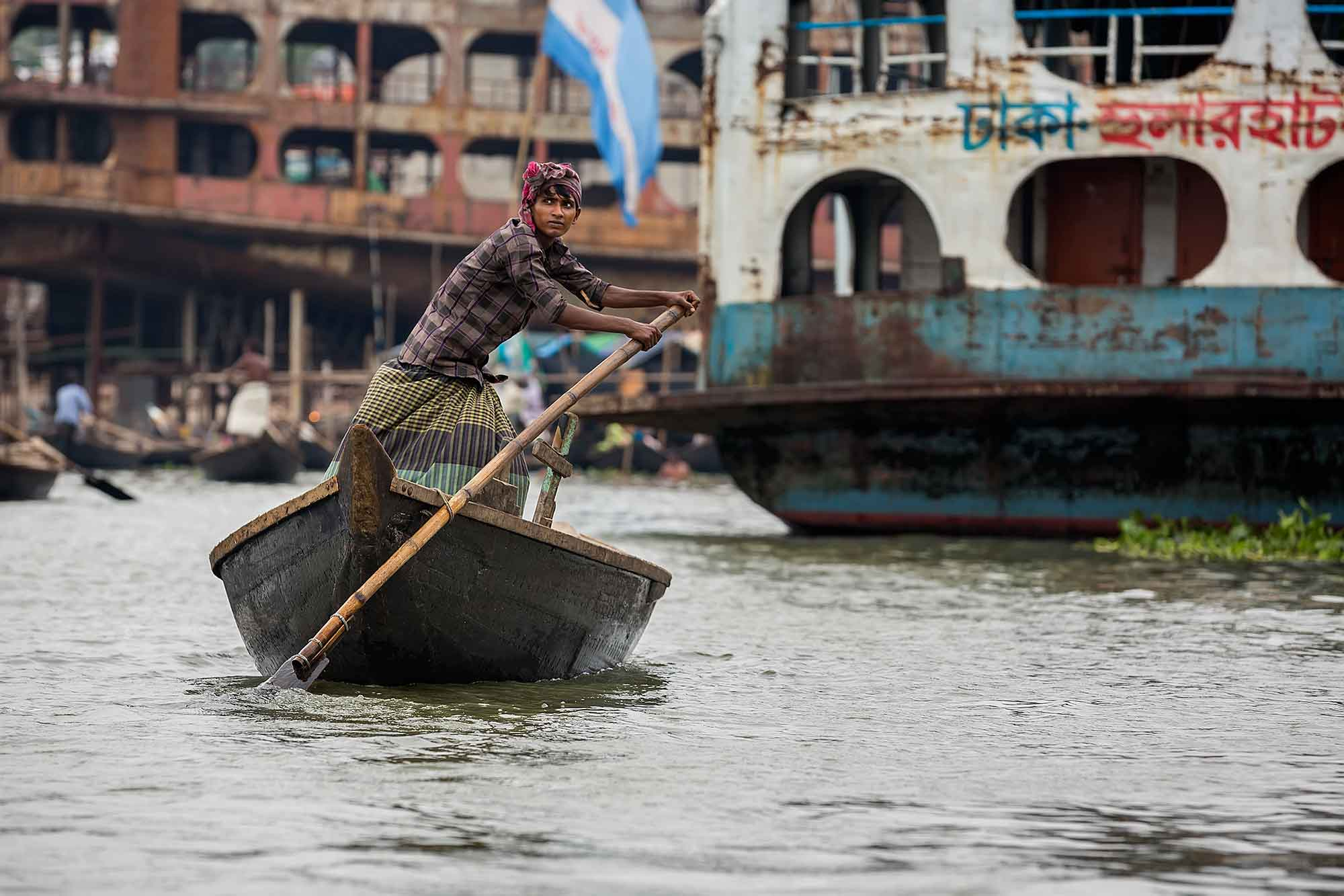 A ferryman taking people across the Buriganga River in his wooden boat. © Ulli Maier & Nisa Maier