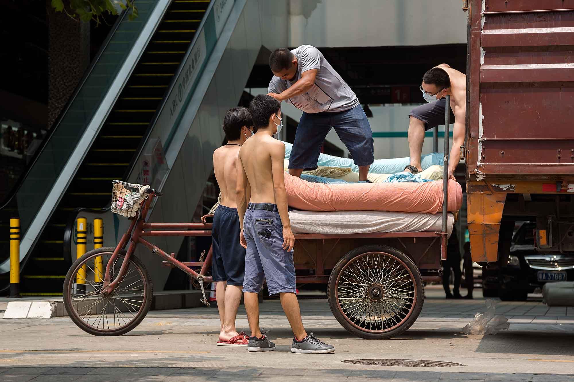 Men unloading a truck in Beijing. © Ulli Maier & Nisa Maier