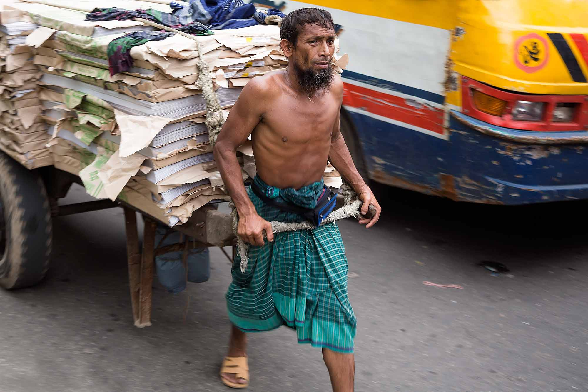 A man pulling a fully loaded cart with leather in the streets of Dhaka, Bangladesh. © Ulli Maier & Nisa Maier