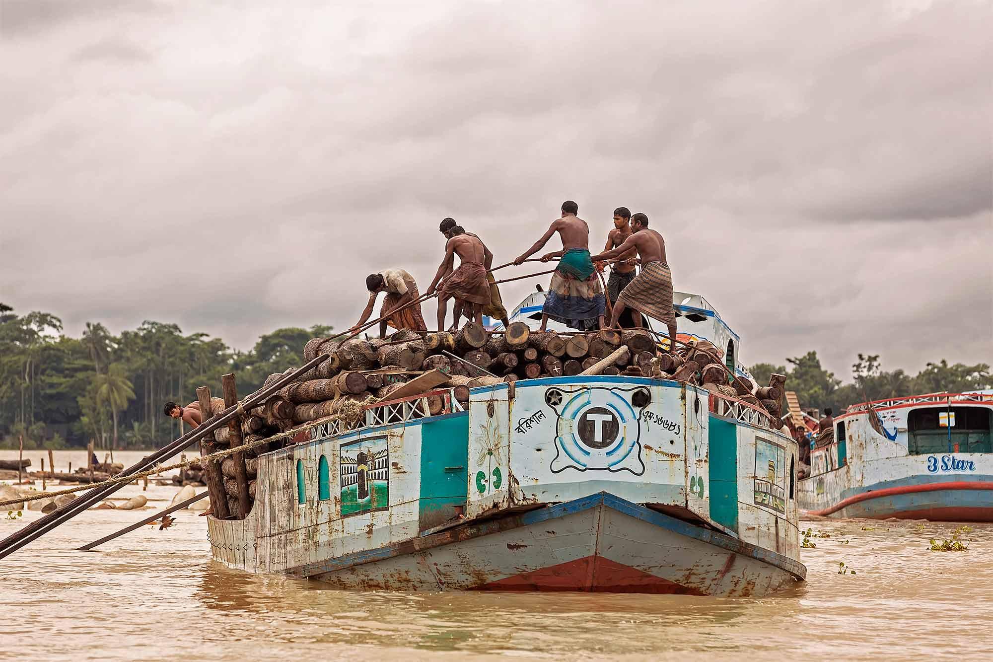 Men loading up a boat with wood trunks in Swarupkati, Bangladesh. © Ulli Maier & Nisa Maier