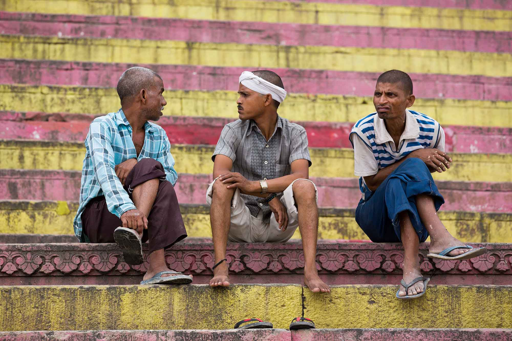 three-men-sitting-ghats-varanasi-india