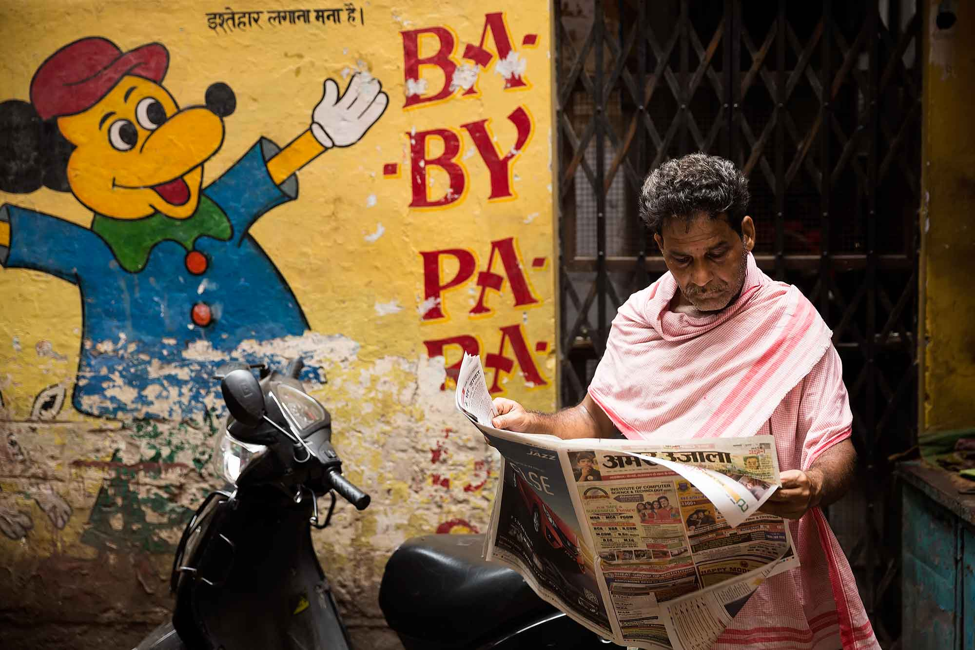 man-reading-newspaper-streets-varanasi-india