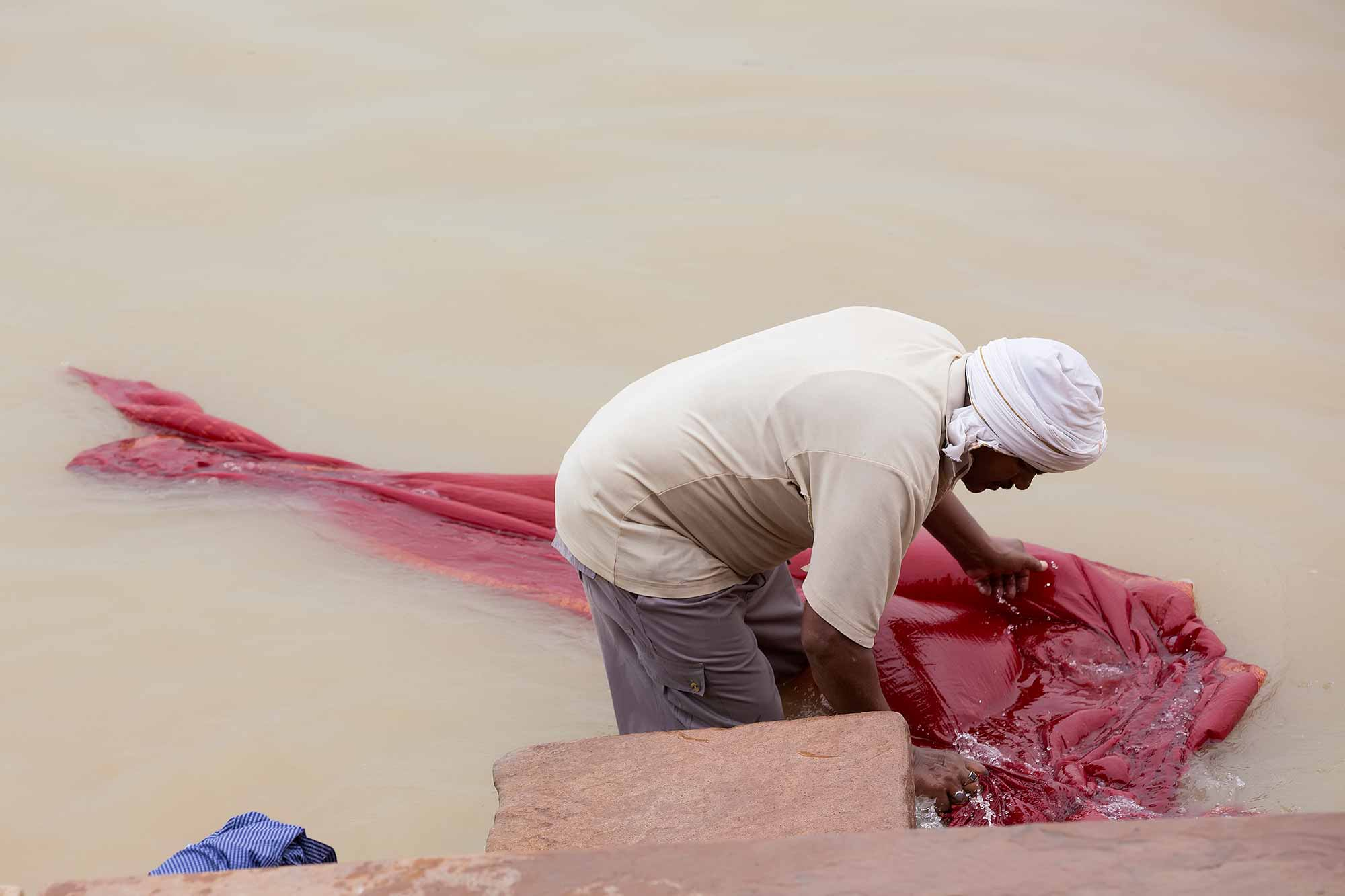 man-washing-clothes-ghats-varanasi-india